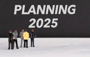 """Menschen stehen vor dem Text """"2025 planen"""""""