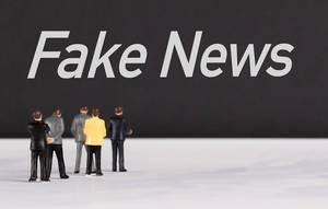 """Menschen stehen vor dem Text """"Fake News / Falschnachrichten"""""""