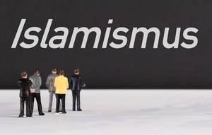 """Menschen stehen vor dem Text """"Islamismus"""""""