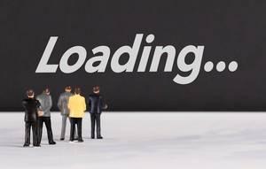 """Menschen stehen vor dem Text """"loading / laden ..."""""""