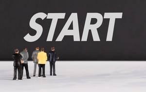 """Menschen stehen vor dem Text """"Start"""""""