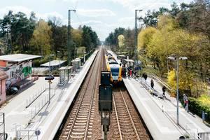 Menschen steigen an einem kleinen Potsdamer Bahnhof in einen Zug, um zu verreisen
