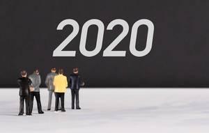 """Menschenfiguren stehen vor einer Wand mit  """"2020"""" als Text"""