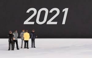 """Menschenfiguren stehen vor einer Wand mit  """"2021"""" als Text"""
