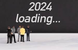 """Menschenfiguren stehen vor einer Wand mit  """"2024 loading"""" als Text"""