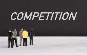 """Menschenfiguren stehen vor einer Wand mit  """"Competition"""" als Text"""