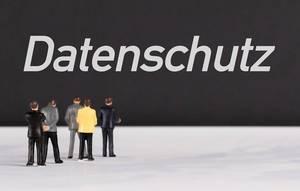 """Menschenfiguren stehen vor einer Wand mit  """"Datenschutz"""" als Text"""