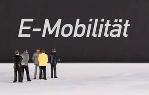 """Menschenfiguren stehen vor einer Wand mit  """"E-Mobilität"""" als Text"""