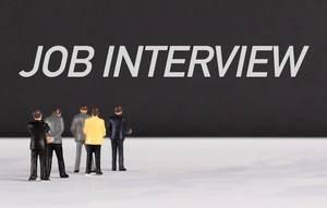 """Menschenfiguren stehen vor einer Wand mit  """"Job Interview"""" als Text"""