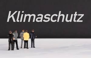 """Menschenfiguren stehen vor einer Wand mit  """"Klimaschutz"""" als Text"""