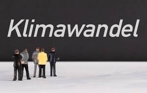 """Menschenfiguren stehen vor einer Wand mit  """"Klimawandel"""" als Text"""