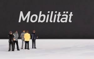 """Menschenfiguren stehen vor einer Wand mit  """"Mobilität"""" als Text"""