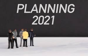 """Menschenfiguren stehen vor einer Wand mit  """"Planning 2021"""" als Text"""