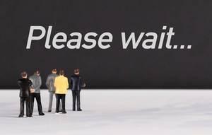 """Menschenfiguren stehen vor einer Wand mit  """"Please wait"""" als Text"""