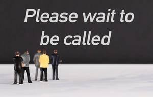"""Menschenfiguren stehen vor einer Wand mit  """"Please wait to be called"""" als Text"""