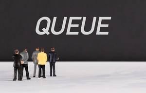 """Menschenfiguren stehen vor einer Wand mit  """"Queue"""" als Text"""