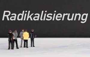 """Menschenfiguren stehen vor einer Wand mit  """"Radikalisierung"""" als Text"""