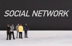 """Menschenfiguren stehen vor einer Wand mit  """"Social network"""" als Text"""