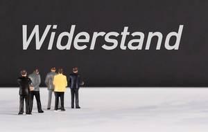 """Menschenfiguren stehen vor einer Wand mit  """"Widerstand"""" als Text"""