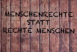Menschenrechte statt rechte Menschen geschrieben auf einer Holzfassade