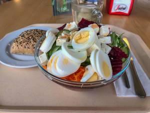 Menu in der Kantine bestehend aus gemischtem Salat mit Karotten, Gurken, Rucola, roter Bete, Fetakäse und Ei, dazu ein Vollkornbrötchen und Tee, bereitgestellt mit Besteck auf beigem Tablett
