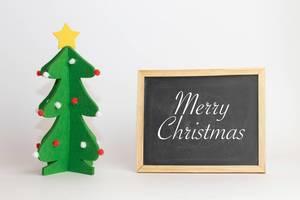 Merry Christmas - Frohe Weihnachten auf einer Schreibtafel mit einem Weihnachtsnbaum