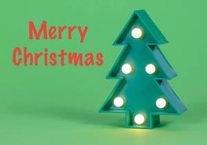 Merry Christmas - red writing on green background with illuminated tree