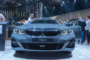 Messebesucher betrachten den Allradkombi BMW 330d xDrive mit Sechszylinderdiesel