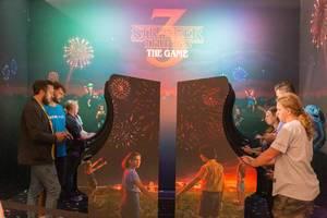 """Messebesucher der Gamescom testen die Science-Fiction-Mysteryserie als Videospiel """"Stranger Things 3 - The Game"""" an Spielstationen im Retrolook"""