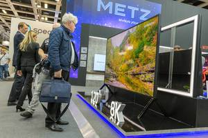 """Messebesucher schauen auf den Sharp Fernseher 8K, mit riesigem 120"""" Bildschirm"""