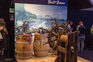 Messestand von Skull & Bones im Piraten-Look mit Rumfässern und Ruder