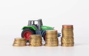 Metal coin stacks and tractor on white background