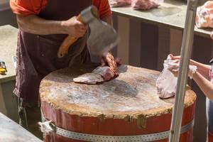Metzger schneidet Fleisch mit einer Axt am Danilovsky Market in Moskau