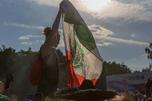 Mexican female soccer fan with flag in hands