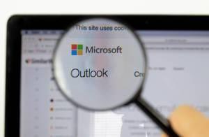 Microsoft-Logo am PC-Monitor, durch eine Lupe fotografiert
