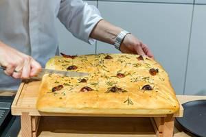 Miele-Backshow auf der IFA: Bettina Seitz von der Kochschule Münster schneidet selbstgebackenes Focaccia-Brot mit Rosmarin auf einem Holzbrettchen