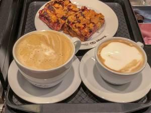 Milchkaffee und Cappuccino mit Pflaumen-Streuselkuchen auf einem Tablet in der Nahmaufnahme