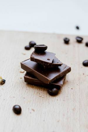 Milk chocolate pieces with coffee beans on wooden board