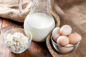 Milk jug with cottage cheese and eggs on burlap