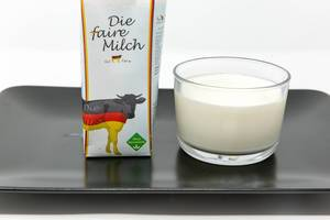 Milk Made in Germany - Fair Milk - not genetically modified - Milk in a glas with packaging on white plate