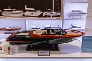 Miniatur eines eleganten Motorboots ausgestellt an Messe, im Hintergrund weitere Modellboote