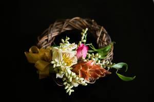 Mit Blumen und Blüten verzierter Kranz eines Blumenmädchens vor schwarzem Hintergrund