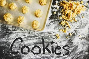 Mit dem Finger in Mehl geschriebenes Wort COOKIES vor noch ungebackenen Keksen und Plätzchenteig