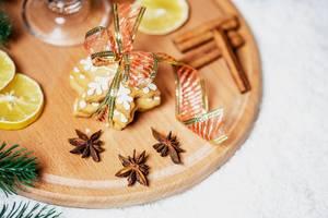 Mit einer Schleife gebundene Zimtsterne mit Zimt, Sternanis, einer Scheibe Zitrone und einem Glas Glühwein auf rundem Brettchen