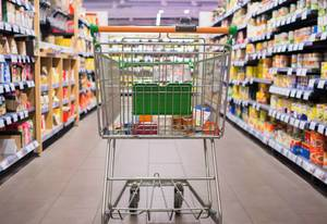 Mit einigen Produkten gefüllter Einkaufswagen steht in Supermarktgang zwischen Regalen