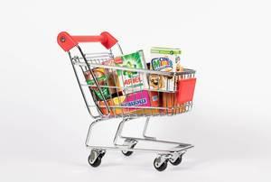 Mit Esswaren, Haushaltsprodukten und Süßwaren gefüllter Einkaufswagen vor weißem Hintergrund