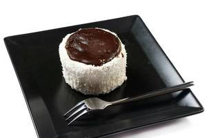 Mit Kokos und Schokolade verzierter Nachtisch mit liegender Gabel auf schwarzem Teller