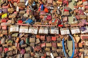 Mit Namen gravierte Schlösser hängen an der Brücke in Köln
