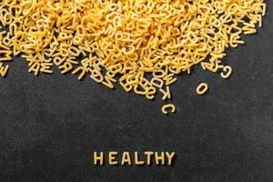 Mit Nudeln geformtes Wort Healthy auf schwarzem Hintergrund neben Pastaberg