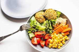 Mit Salat und Gemüse angerichtete Buddha-Schüssel mit Falafel und Hummus vor weißem Hintergrund